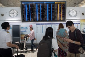 An electronic billboard shows flight information at the departure hall of Hong Kong International Airport today, after more than 100 flight cancellations