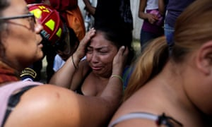 Family members react as they wait for news of their loved ones after a fire broke at the Virgen de Asunción home.