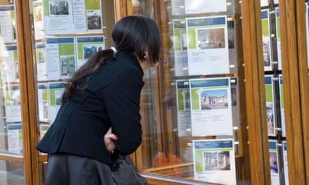 Young woman looking at houses in estate agent window