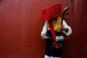 An artist in traditional costume waits to perform in pre-celebrations for the Dalai Lama's 82nd birthday in Kathmandu, Nepal