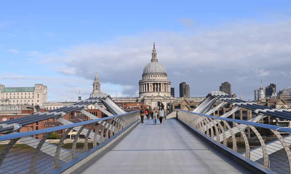 Pedestrians cross the Millennium Bridge in a quiet London, as it enters a new phase of lockdown.