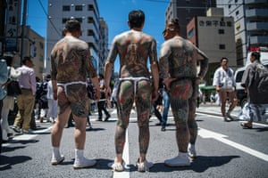 Heavily tattooed Japanese men chat in the street near Asakusa Temple