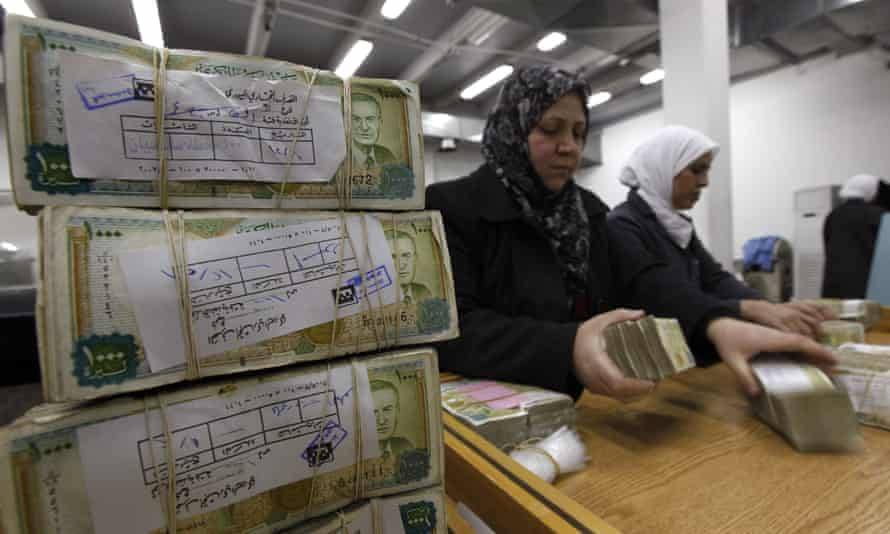 Syrian central bank staff stack wads of Syrian pounds in Damascus