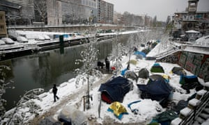 Migrants at a makeshift camp blanketed by snow at the Saint-Martin canal in Paris.