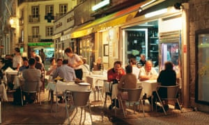 People sit at restaurant tables in the Baixa district of Lisbon