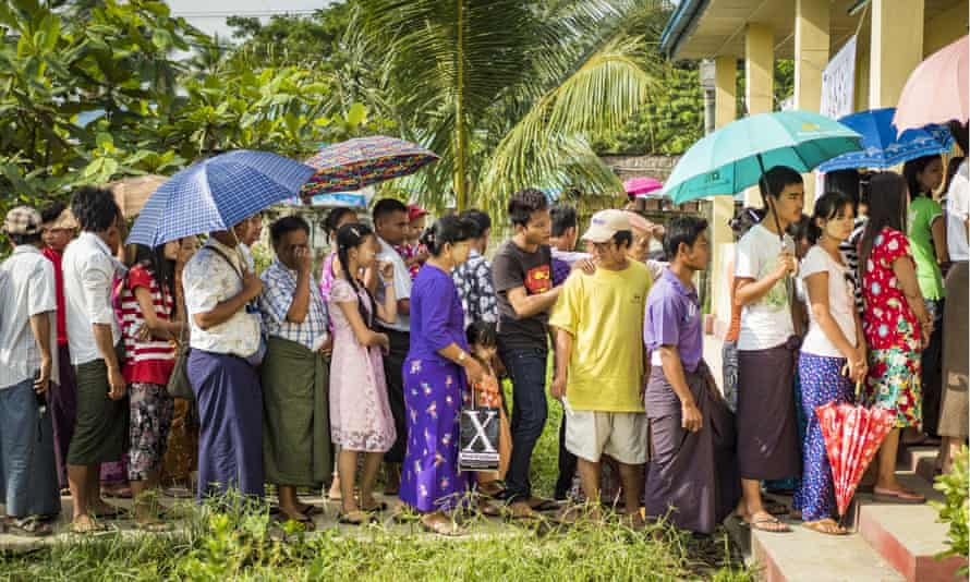 People stand in line at a polling station in North Okkalapa near Yangon on Sunday