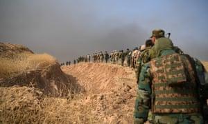 Kurdish peshmerga soldiers walk alongside a trench near Mosul, Iraq