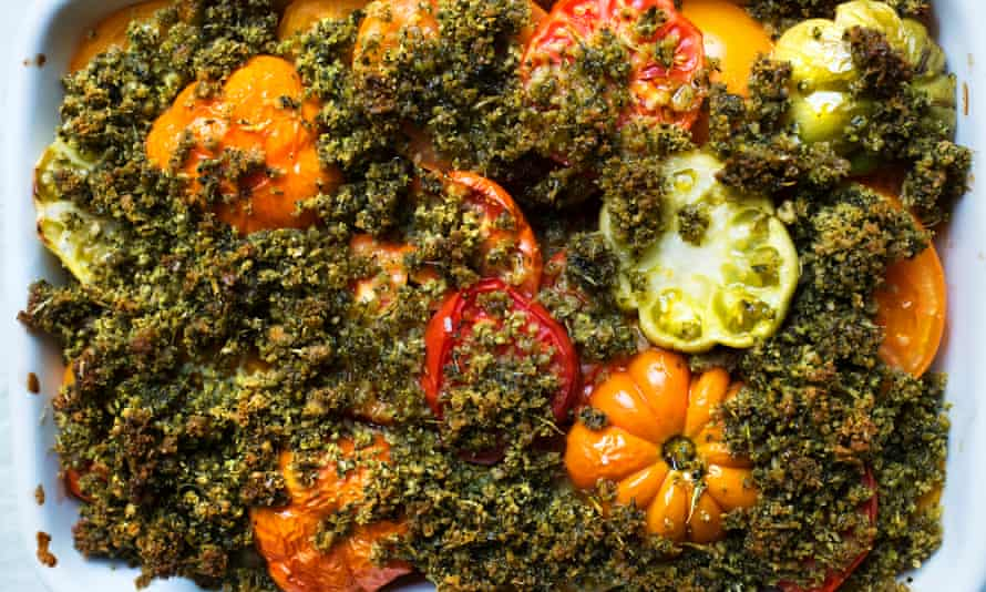 Large orange, red and green tomato slices protruding through a dark green basil crumb mixture