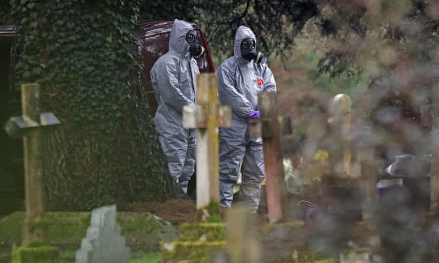 Forensic officers wear gas masks at the cemetery in Salisbury, Wiltshire, where the wife and son of the former Russian double agent Sergei Skripal were laid to rest.