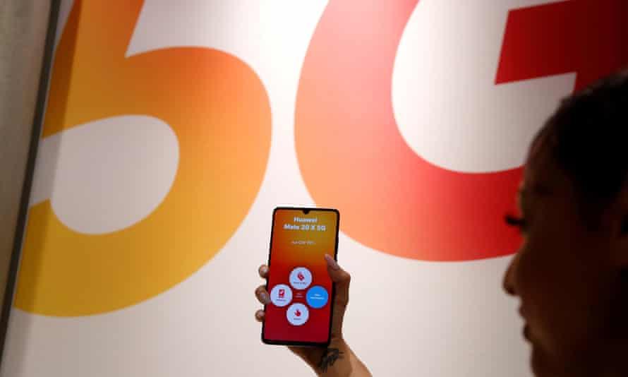 An employee displays a Huawei 5G smartphone.