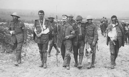 A wounded German prisoner of war assisting wounded British soldiers on the Somme front.
