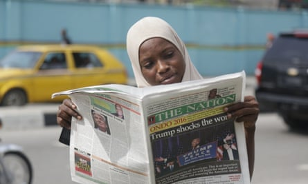 A woman in Lagos reads a newspaper reporting on Trump's victory in November 2016