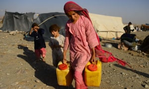 A girl forced to leave home by drought carries water obtained from a tanker at a camp in the Injil district of Afghanistan's Herat province