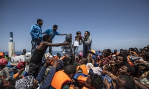 Migrants wait aboard a crowded wooden boat during a rescue operation in the Mediterranean