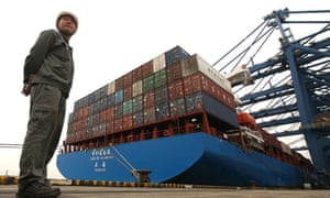 Security personnel monitors shipping containers at a port in Dongguan, China.