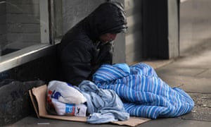 A homeless man is seen in a sleeping bag on a pavement in London