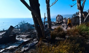 A firefighter inspects the remains of a beachside luxury home along the Pacific Coast Highway community of Point Dume in Malibu