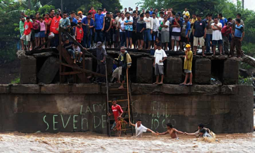 People try to cross a river as others look from a damaged bridge in El Salvador in the wake of Tropical Storm Agatha, which led to consumption per head falling by 5.5% and increased poverty by 14%.