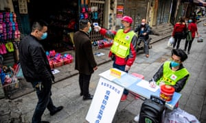 A man measures people's body temperature at a roadblock in Guangzhou, China