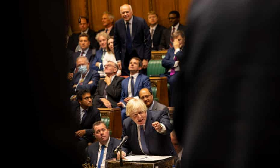 Boris Johnson glimpsed on the other side of the Commons chamber framed between the shoulders of two opposition MPs, gesturing at the dispatch box while the Tory MP Iain Duncan Smith rises behind him, seeking to intervene