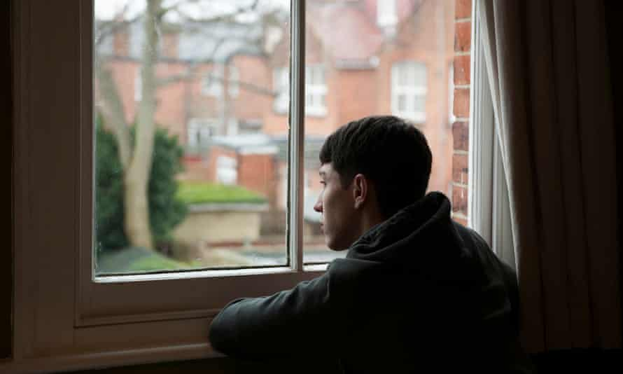 Teenage boy looking out of window