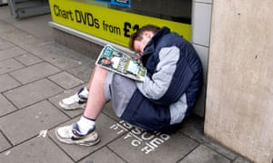 A Big Issue seller asleep on his pitch