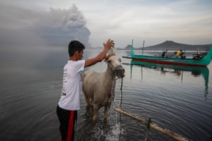 A villager washes his horse while the volcano erupts in the background