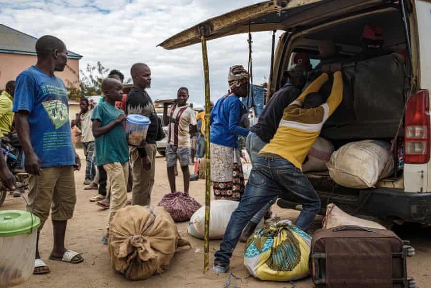 Men pack displaced people's luggage into a minibus at the bus station