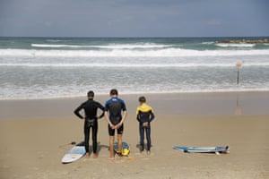 Netanya, Israel Surfers stand still on a Mediterranean beach