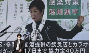 A man wearing a protective mask walks in front of a public tv screen showing Tokyo governor, Yuriko Koike, speaking at a press conference