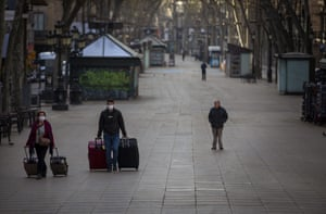 People wearing masks drag their suitcases along La Ramblas, Barcelona, Spain
