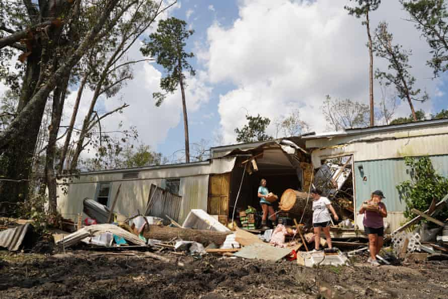 People clean out a storm damaged hom in Springfield, Louisiana.