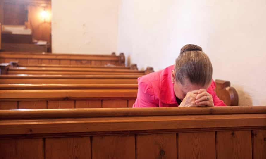 Woman prays during a service at St John the Baptist church in Hope Bagot, Shropshire