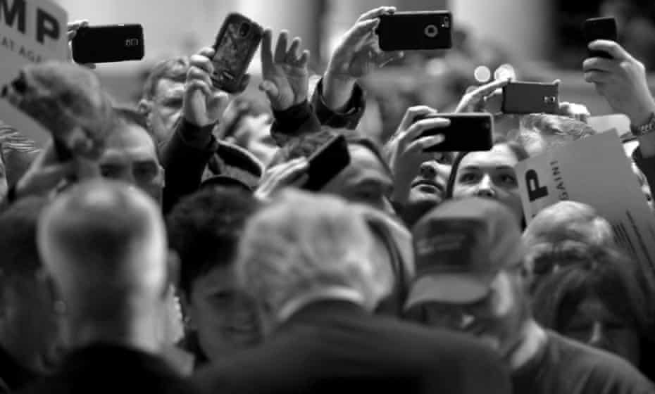 Supporters take photos of US Republican presidential candidate Trump at a campaign event at the Veterans Memorial Building in Cedar Rapids.