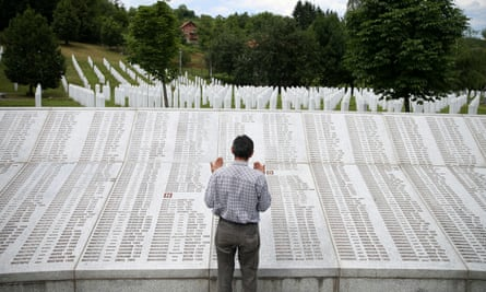 A genocide survivor prays near the graves of his father and two brothers at the memorial centre near Srebrenica
