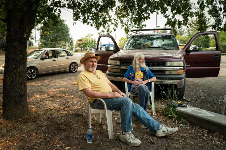 Jim Laughlin and Jean-Pierre sit outside in a community park listening to wildfire updates on the radio in Forestville.