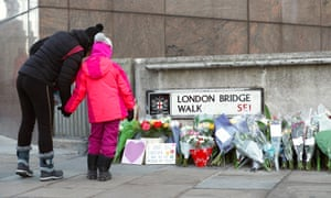 Passersby stop to look at flowers left at London Bridge in central London following the murder of Jack Merritt and Saskia Jones by Usman Khan.