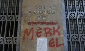 Graffiti covers a Bank of Greece sign making it read 'Bank of Merkel'