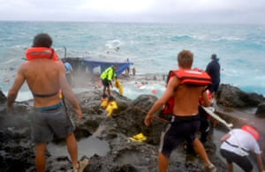 People clamber on the rocky shore of Christmas Island during a rescue attempt as a wooden boat packed with asylum seekers boat breaks up in 2010.