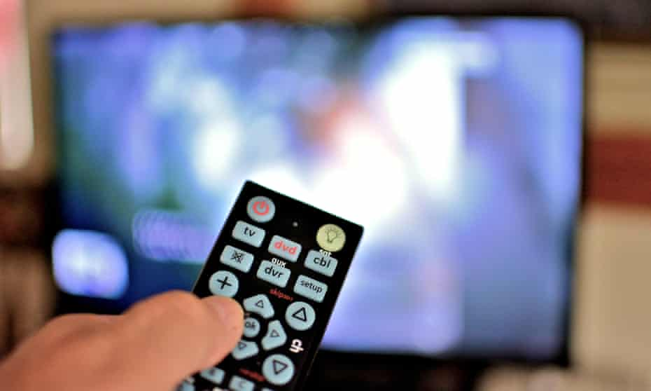 Closeup view of a television remote in hand with the tv blurred in the background.