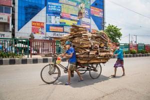 A masked man pushes an overladen rickshaw along a wide but quiet street in Dhaka