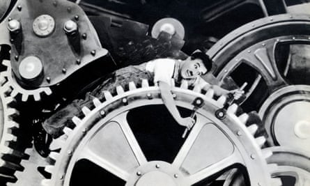 Charlie Chaplin lying across a large cog in the 1936 black and white film Modern Times.