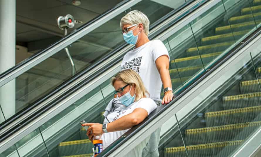 People wearing masks on escalator.