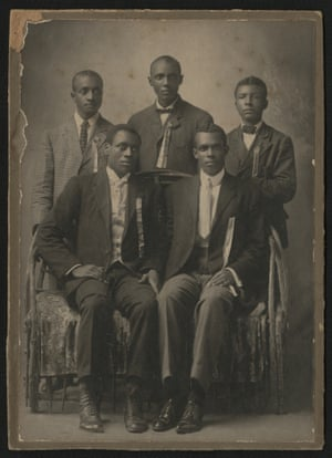 Five well-dressed African American men, two seated on bench and three standing behind