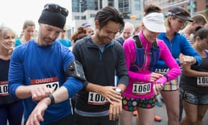 Marathon runners prepare their smartwatches at the start of a race