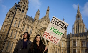 A student protests outside parliament in Westminster, against spending cuts, tuition fees and student debt.