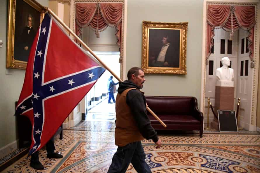 A member of a pro-Trump mob carries a Confederate battle flag on the second floor of the US Capitol.