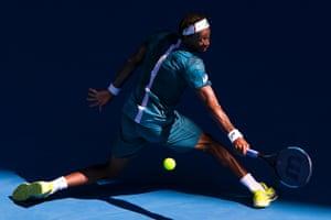 Gael Monfils stretches for a return against Novak Djokovic.