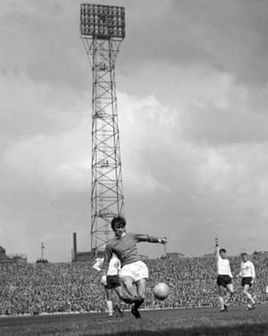 Best crosses the ball with the Old Trafford floodlights prominently in the background in a season when United went on to claim the title