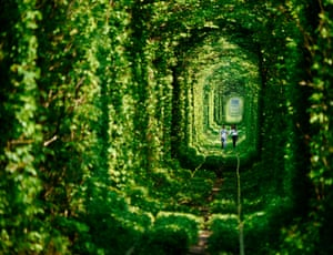 A young couple walk through the 'tunnel of love' near the town of Klevan in Ukraine. The tunnel is a two-mile section of private railway that serves a local factory. A train runs through it three times a day.